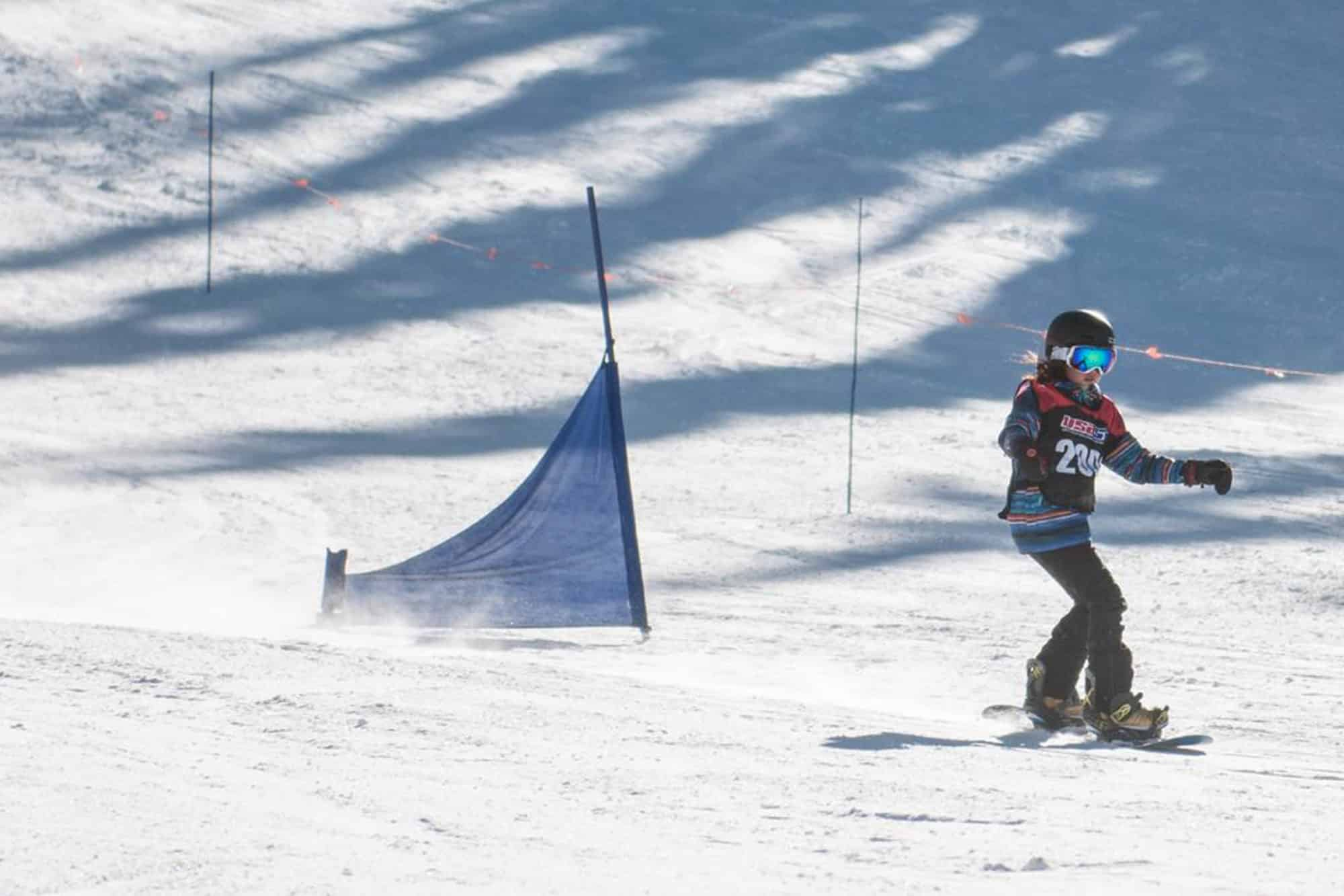 Snowboard racer turning around gates